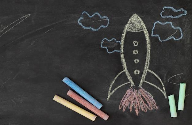 Cohete dibujado de tiza en la pizarra. concepto de regreso a la escuela