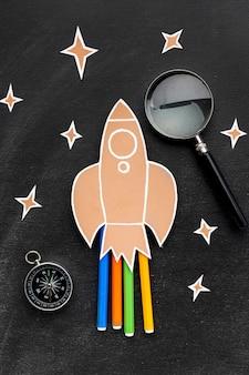 Cohete de regreso a la escuela con lupa y lápices
