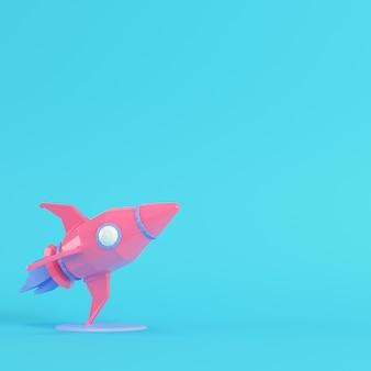 Cohete rosa con soporte sobre fondo azul brillante en colores pastel. concepto de minimalismo