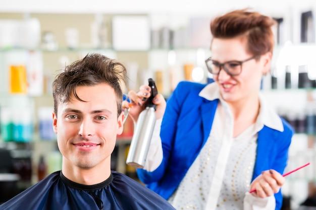 Coiffeur femenino cortando el cabello de los hombres en peluquería
