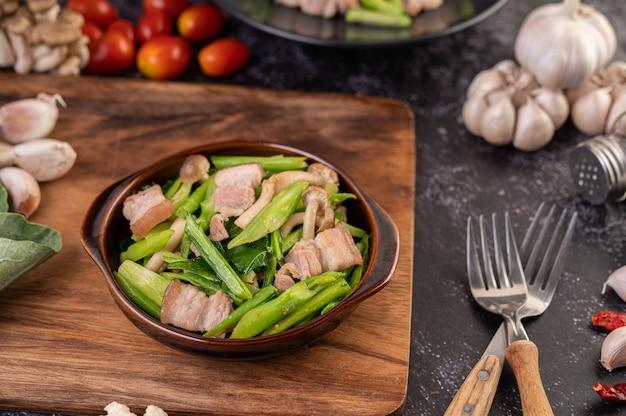 Col rizada salteada y panceta de cerdo en un plato colocado sobre una placa de madera.