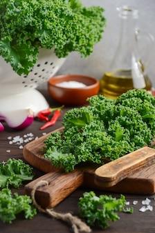 Col rizada verde fresca con aceite de oliva y especias, lista para cocinar.