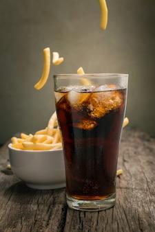 Cola con los cubos de hielo colocados en la tabla de madera con el fondo de las patatas fritas.