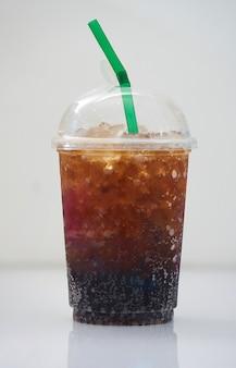 Cola helada en taza plástica transparente con paja verde sobre fondo blanco con sombra