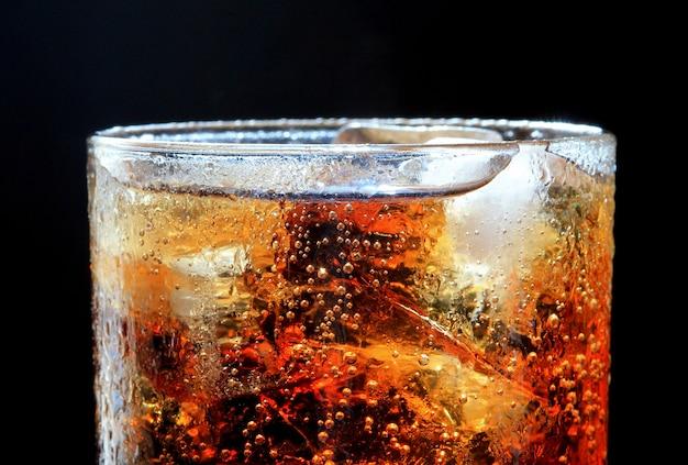 Cola y hielo, burbuja en vaso.