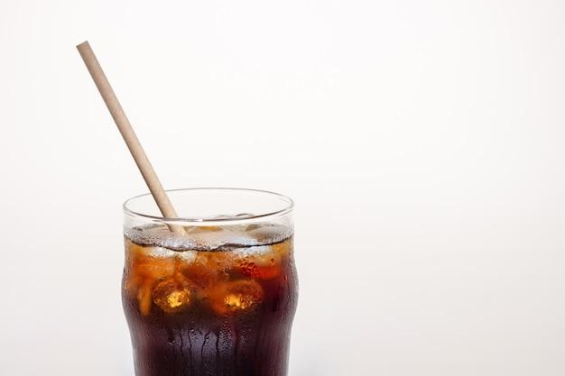 Cola con hielo en un vaso de vidrio, una copia del espacio