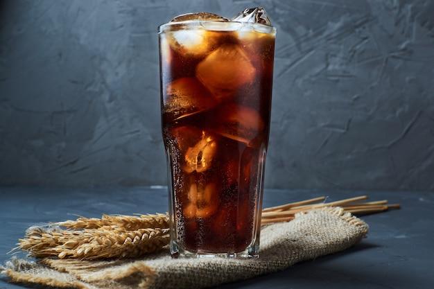 Cola oscura fría con cubitos de hielo y trigo