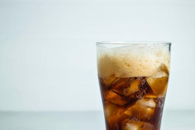 Cola, refrescos en un vaso sobre un fondo blanco.