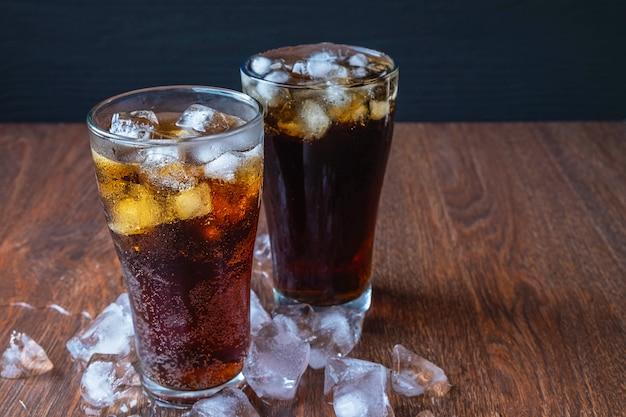 Cola en vaso y cubitos de hielo