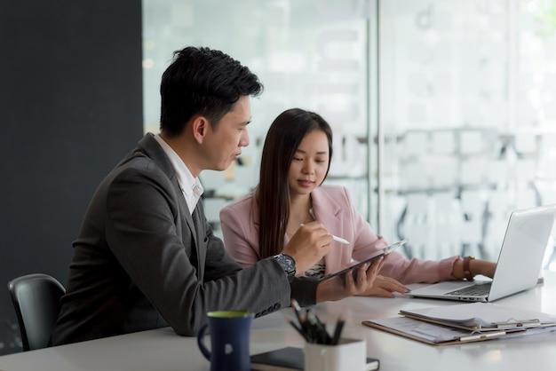 Colaboración de empresario y empresaria asiática usando laptop y una tableta en la oficina.