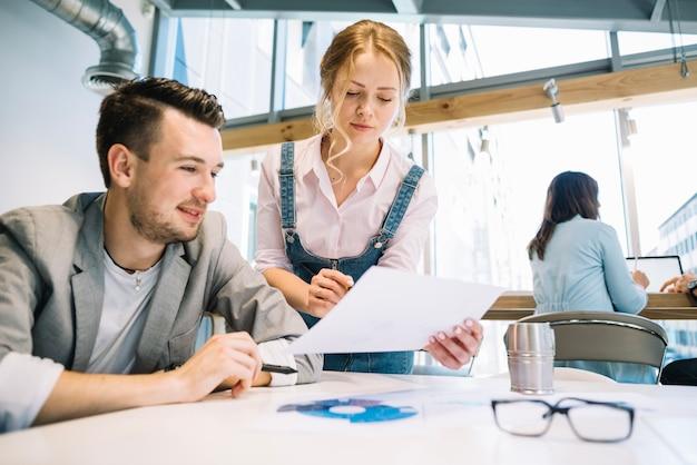 Colaborando hombre y mujer con papeles