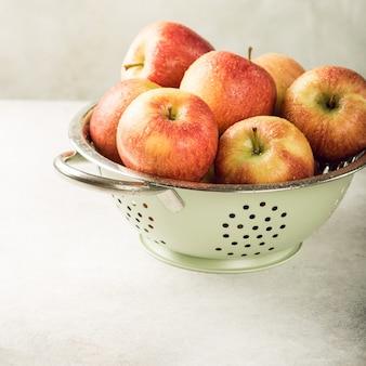Colador con manzanas rojas maduras.