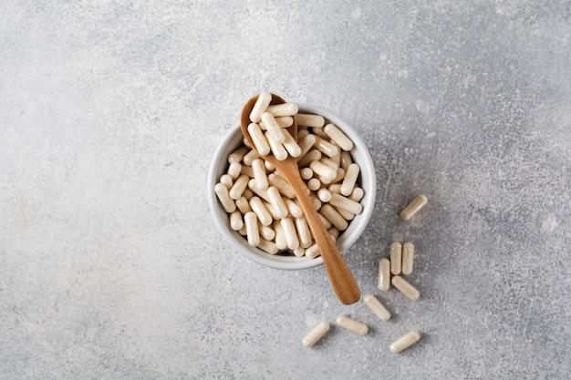 Colágeno cerrado en cápsulas y una cuchara de madera para alimentos dietéticos en un recipiente de cerámica sobre una vieja mesa de hormigón gris. endecha plana con espacio de copia.