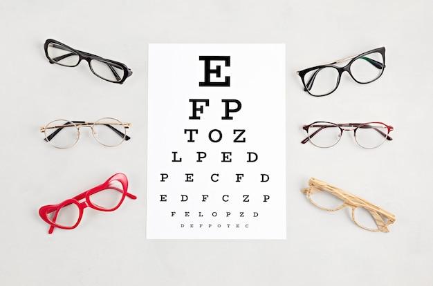 Colección de anteojos con mesa de prueba ocular. tienda de óptica, selección de gafas, examen ocular, examen de la vista en el óptico, concepto de accesorios de moda. vista superior, endecha plana