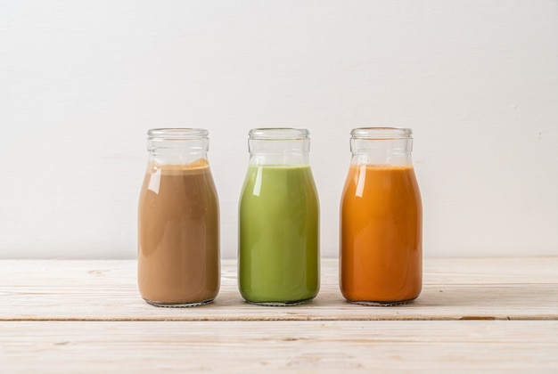 Colección de bebidas té con leche tailandés, té verde matcha con leche y café en botella sobre madera
