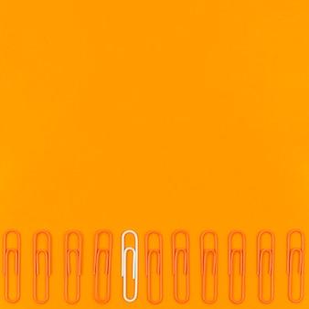 Colección de clips de papel con solo uno blanco y espacio de copia
