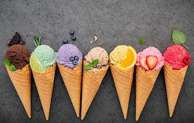 Colección de conos de helado plano sobre fondo de piedra oscura.