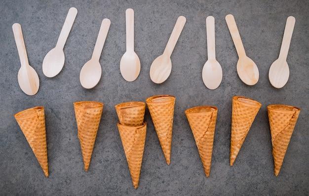 Colección de conos de helado planos laicos sobre fondo de piedra oscura.