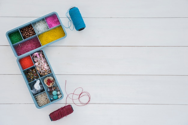 Colección de cuentas en estuche azul con carrete de hilo azul y púrpura brillante en escritorio blanco