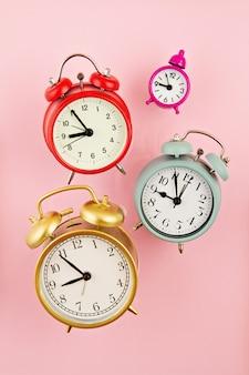 Colección de despertadores coloridos brillantes sobre el fondo rosa
