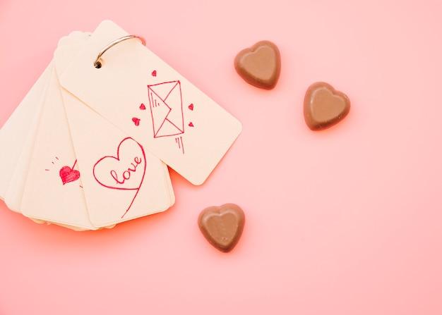 Colección de etiquetas con diferentes imágenes cerca de caramelos de chocolate.