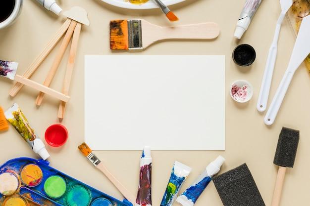 Colección de herramientas de artista y hoja de papel.