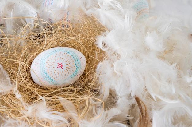 Colección de huevos de pascua en heno entre montón de plumas