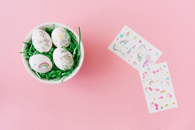 Colección de huevos de pascua en un tazón cerca de pegatinas
