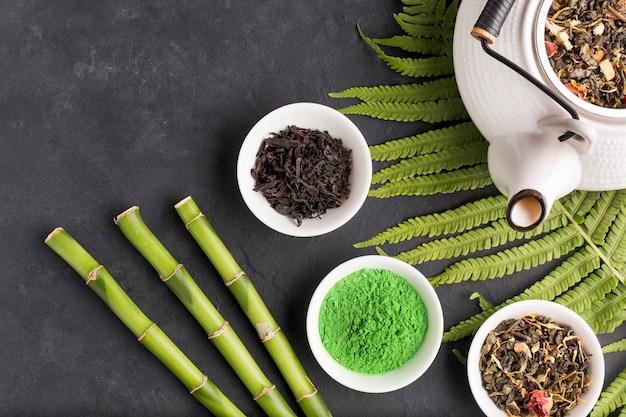 Colección de ingrediente de té seco aromático en superficie negra