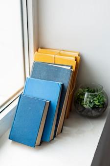 Colección de libros coloridos con planta.