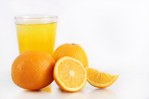 Una colección de naranjas y un vaso de hielo fresco de naranja