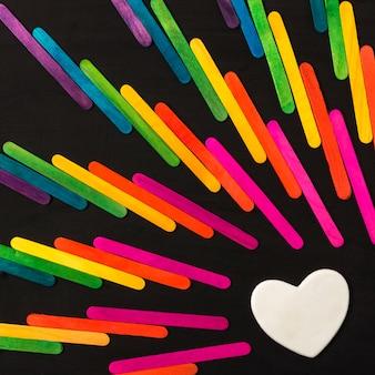 Colección de palos en colores lgbt brillantes y corazón decorativo.