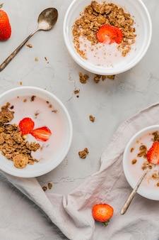 Colección de platos de desayuno con granola y fresa.