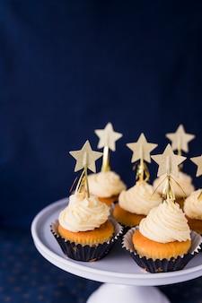 Colección de sabrosos pasteles con crema de mantequilla y estrellas en el stand.
