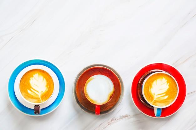 Colección de taza colorida de café del arte del latte en la tabla de mármol blanca.