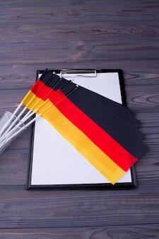 Colección de tiro vertical de banderas de alemania y portapapeles con papel