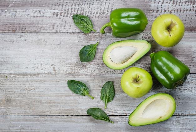 Colección de vegetales verdes sobre fondo de madera, pimientos, manzana, espinacas y aguacate.