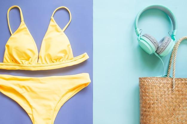 Colección de verano, bikini de color amarillo, auriculares y bolso de playa de paja. vacaciones de verano