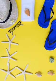 Colección de verano, pez estrella, chanclas azules, gorro, toalla blanca y flor de frangipani sobre fondo amarillo