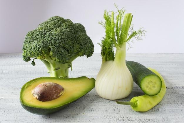 Colección de verduras frescas sobre fondo blanco rústico, brócoli, hinojo, aguacate, pepino, pimienta