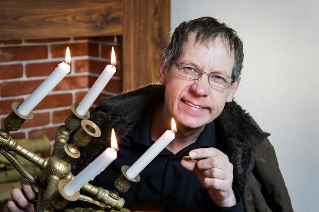 El coleccionista mira su riqueza con velas encendidas.