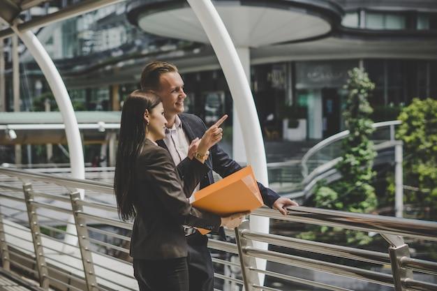 Colega de negocios hablando y viendo documentos al aire libre