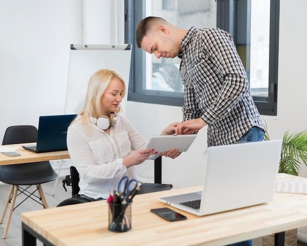 Colega que muestra a la mujer en silla de ruedas algo en tableta en el trabajo