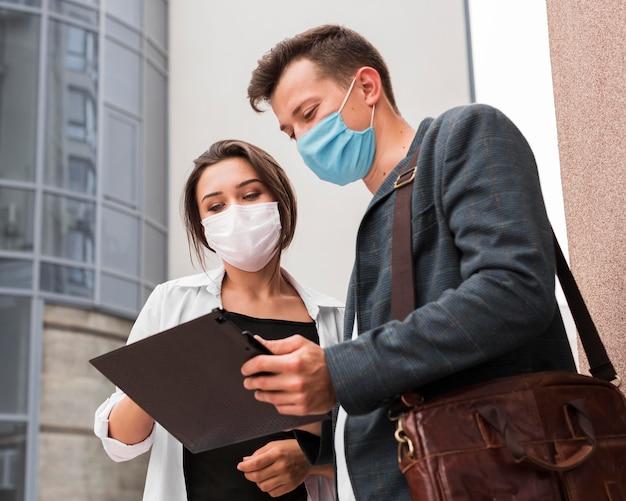 Colegas al aire libre durante la pandemia mirando el bloc de notas con máscaras faciales