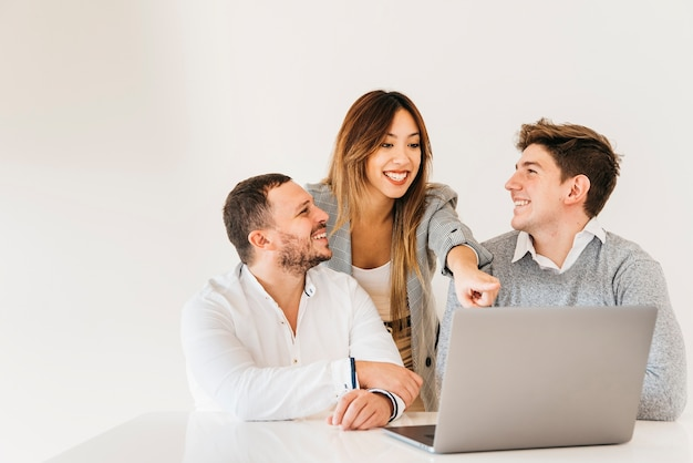 Colegas alegres que miran proyecto en la computadora portátil en la oficina