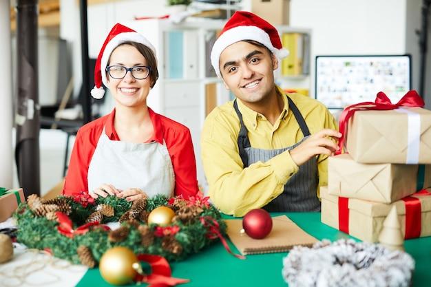 Colegas alegres con regalos y corona de navidad