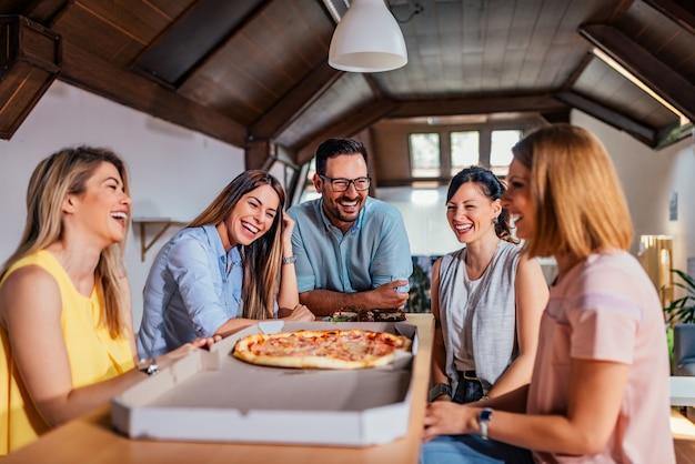 Colegas almorzando, comiendo pizza.