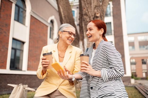 Colegas amistosos. closeup retrato de dos colegas elegantes y guapos sentados al aire libre con un teléfono inteligente y tazas de café de papel mientras se reía