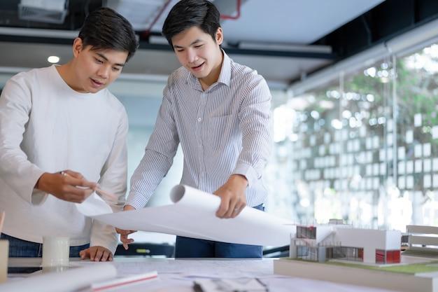 Colegas asiáticos jovenes del arquitecto que discuten sobre planes de la construcción en modelo y tableta en la oficina del emplazamiento de la obra. arquitecto utilizando el concepto de tecnología.