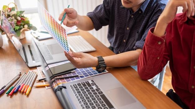 Colegas asiáticos que dibujan bosquejos del dibujo en la computadora portátil gráfica.